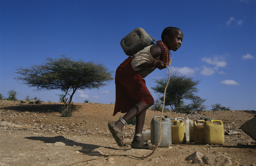 A young Ariaal girl carries a container of water pulled from a well.